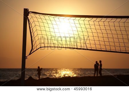 Beach sunset with silhouette of people and beachball net in foreground.