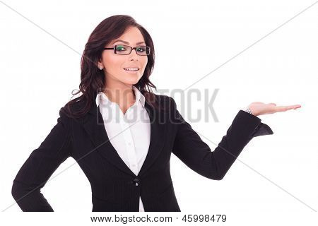 young business woman is holding something imaginary in her palm, while smiling to the camera. on white background