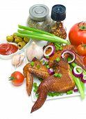 Smoked chicken wings fresh vegetables ketchup olives and spices on a white background. vertical photo poster