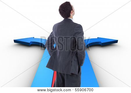 Businessman standing with hands on hips against bright blue room with windows