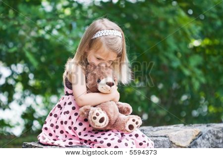Child Kissing and Hugging Her Bear