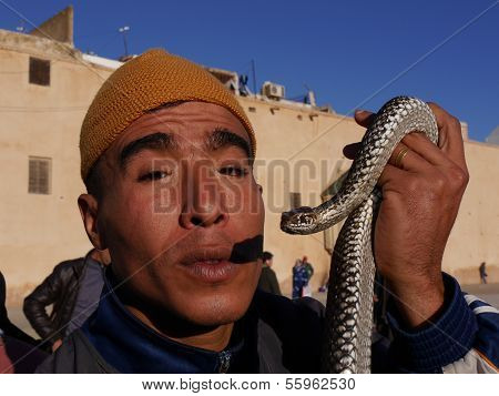 Close-up portrait of Moroccan snake charmer holding snake