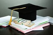 Money for graduation or training on wooden table on grey background poster