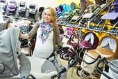Young pregnant woman choosing baby carriage or pram buggy for newborn at shop store poster