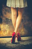 woman legs in red high heel shoes and short skirt outdoor shot against old metal door poster