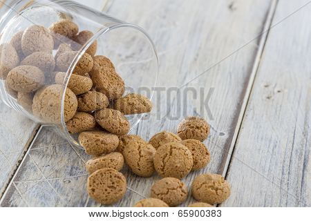 Traditional italian amarettini cookies in a glass on a wooden table poster