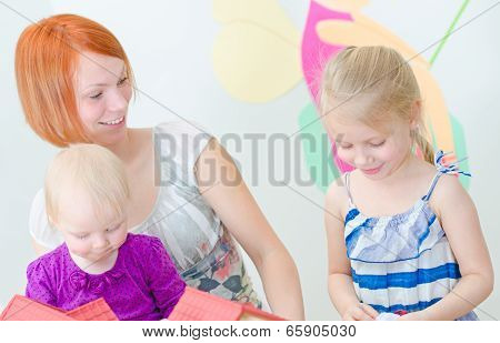 Children And Their Mother Playing With Dollhouse.