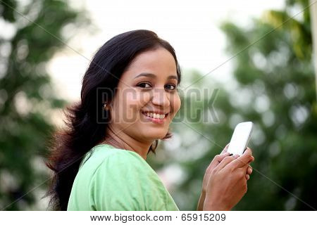 Happy Young Woman Text Messaging At Outdoors