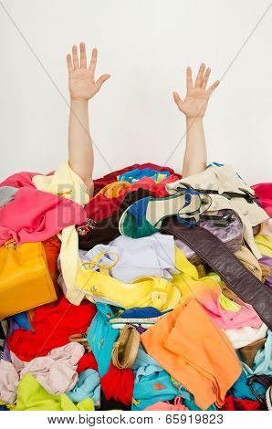 Man hands reaching out from a big pile of clothes and accessories.