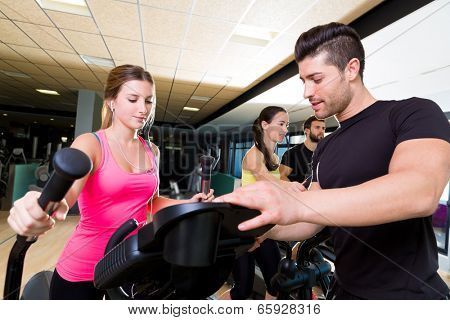 Aerobics elliptical walker trainer personal trainer man at fitness gym workout