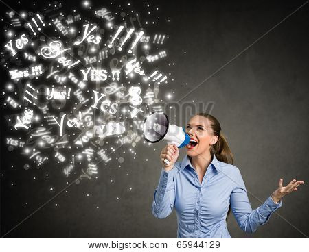 Young woman screaming yes into a megaphone