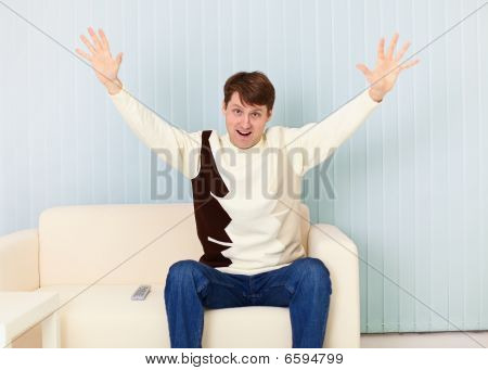 Young Man Exults Sitting On Sofa - Sports Fan