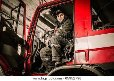 Fireman behind steering wheel of a firefighting truck