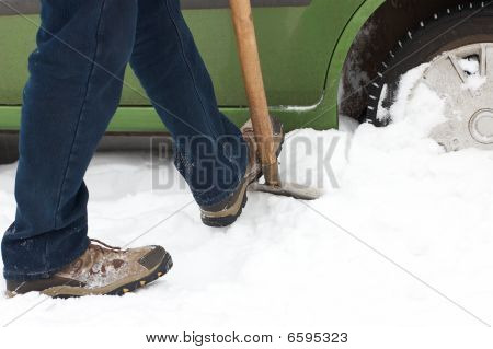 Man Digging Car Wheels From The Snow