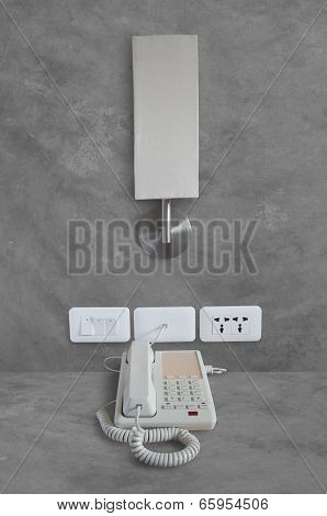 Telephone With Lamp On Concrete Wall