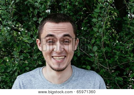 Young man with a goatee beard having a good laugh at a funny joke raising his eyebrows in mirth, standing against a leafy green tree
