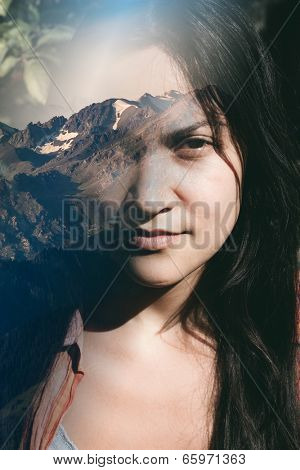 Close up of the face of a beautiful young woman dreaming of the countryside looking at the camera with a faraway meditative look with a vision of a scenic landscape superimposed