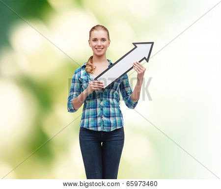 happiness, direction and people concept - smiling young woman arrow poiting up over green background