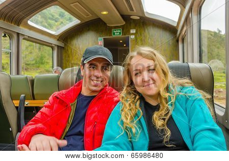 Young inter ethnic couple traveling in panoramic train to Machu Picchu
