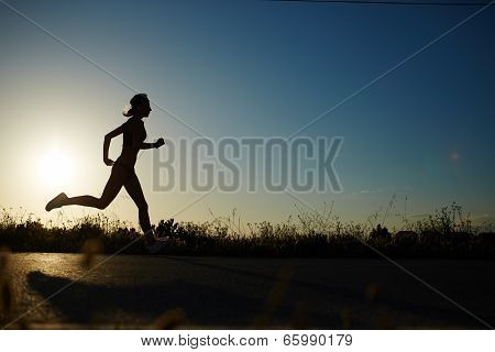 Silhouette of athletic girl running down the road to a sunset poster