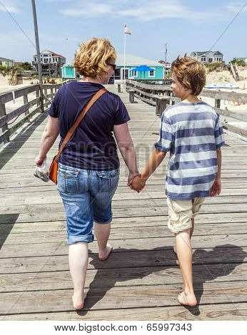 Mother And Son Walking Hand In Hand At Famous Pier