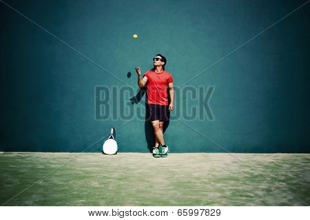 Handsome man standing on the court and playing paddle ball
