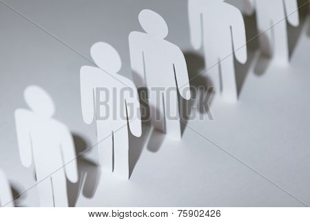 Close up of group of paper-men standing in a row. Lots of copies of one paper man, isolated on white