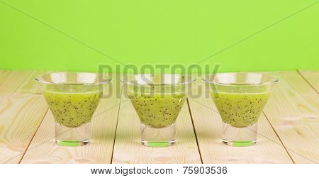 poster of Kiwi juice on the wooden desk and on the green background