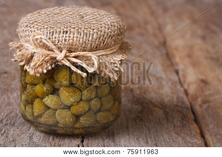 Capers In A Glass Jar Closeup On A Wooden. Horizontal