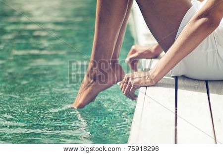 Woman dipping her toes in the ocean as she sits on the edge of a wooden deck or jetty, closeup view of her legs
