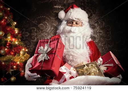 Christmas concept with Santa Claus in costume holding gifts. Dark pattern as background