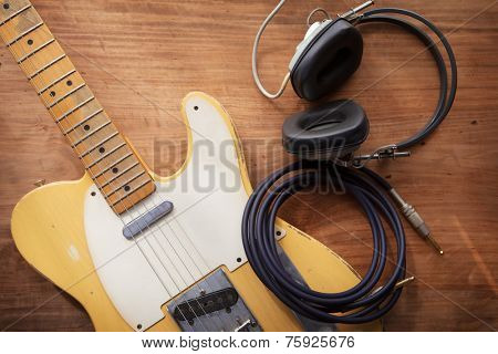 Guitar recording. An electric guitar, and a professional use headphones on a rustic or bare wooden table, with by-the-window type warm light coming in.  poster