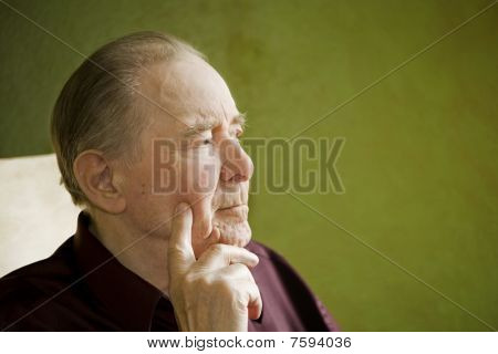 Elderly Man In Rocking Chair Looking Out Sunny Window