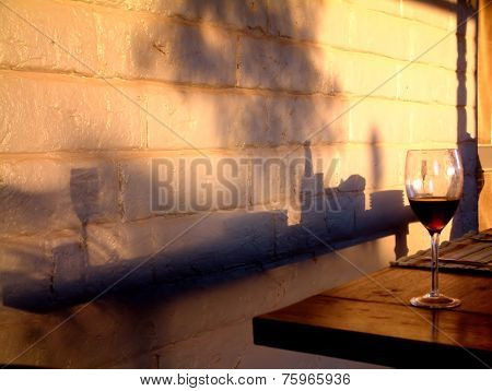 Wine glass on table with shadows on mud brick background