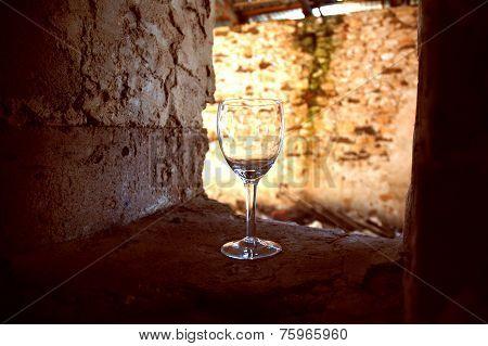 Empty Wine Glass in window ledge  of old cellar ruin