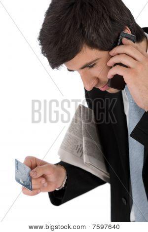 Młody biznesmen posiadania telefonu komórkowego i karty kredytowej