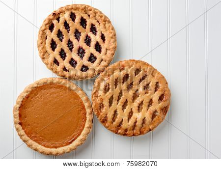 High angle shot of three pies, apple, pumpkin, and cherry. Horizontal format on a white beadboard surface. The pies are favorites for the  American Holidays, Thanksgiving and Christmas.