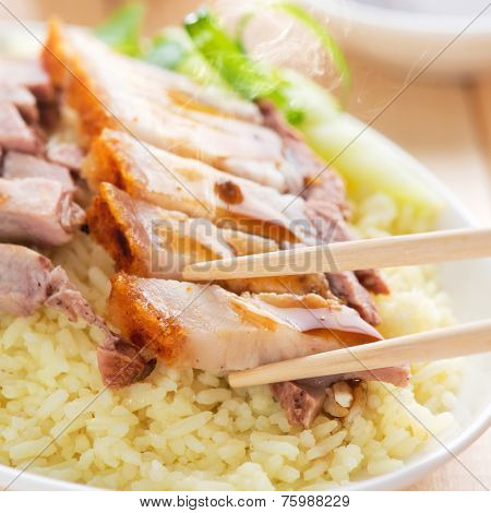Chinese roasted pork served with soy and seafood sauce. Hong Kong cuisine. Close up on meat and chopsticks. Fresh cooked with hot steam and smoke.