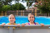 kid girls swimming in the pool in backyard happy poster