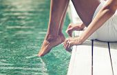 Woman dipping her toes in the ocean as she sits on the edge of a wooden deck or jetty, closeup view of her legs poster