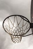 Look at the heaven through a basketball hoop. Gloomy background. poster