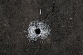 Bullet hole in glass on dirty grungy black background poster