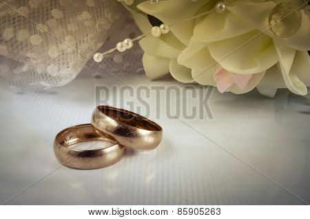 Two Wedding Rings Lie On A Light Horizontal Surface Against A Bouquet Of Flowers.