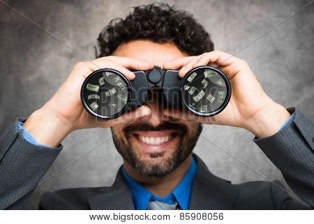 Businessman using binoculars, money reflected in the lens