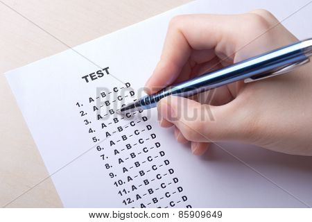 Close Up Of Hand Filling Test Score Sheet With Answers