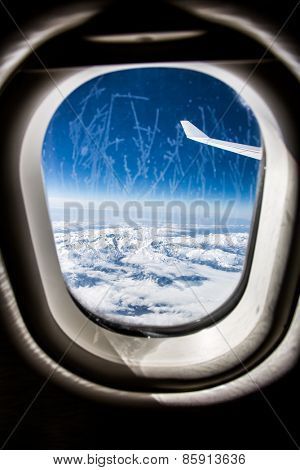 Classic image through aircraft window onto jet engine. Frost on the glass window. Focus on the wing of the aircraft.