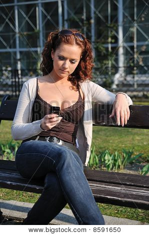 Young Woman On Bench Typing In Mobile Phone