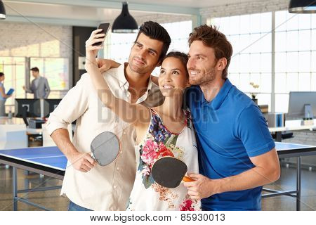 Young companionship making a selfie in ping pong hall. poster