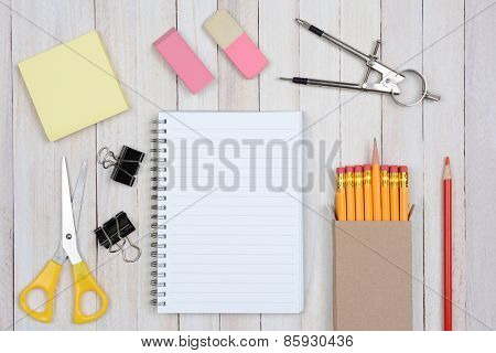 A group of items typically found in a school desk. Items include: erasers, pencils, compass, scissors, paper, note pad, paper clips, shot from a high angle.