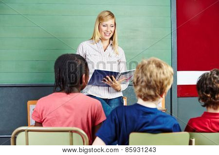 Teacher in elementary school class reading from a notebook
